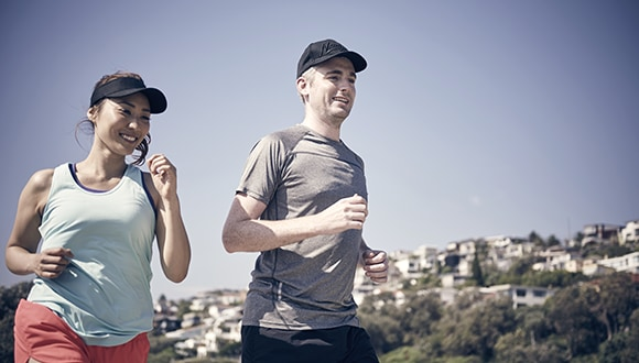 A photo of two people jogging (Female to the left and Male on the right)