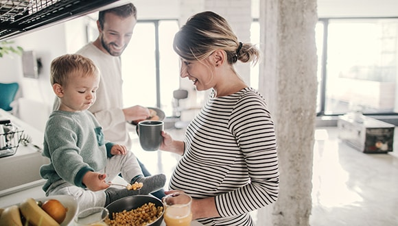 Couple cooking in the kitchen with their young child