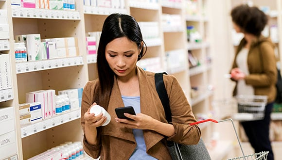Woman in pharmacy researching medicine on phone