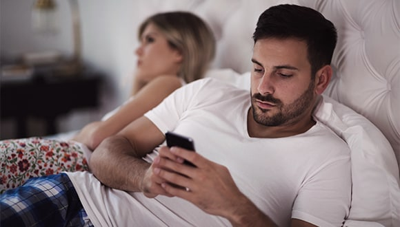 Man with anxiety looking at phone in bed
