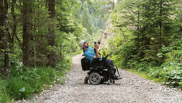 Man in a wheelchair travelling through the wilderness